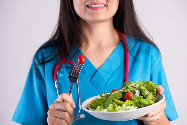 Sourire médecin femme avec stéthoscope mangeant une salade fraîche