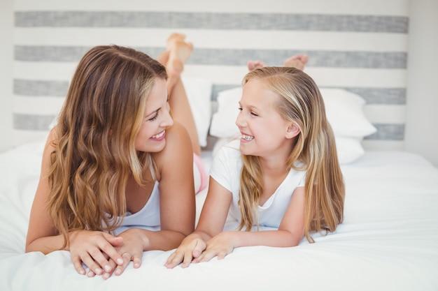 Sourire mère et fille allongée sur le lit