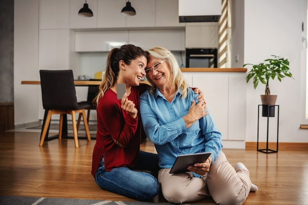 Sourire mère et fille assise sur le sol à la maison et faire du shopping en ligne.
