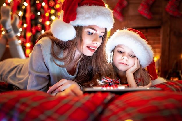 Sourire, mère, fille, santa, chapeaux, pyjamas, regarder, drôle, vidéos