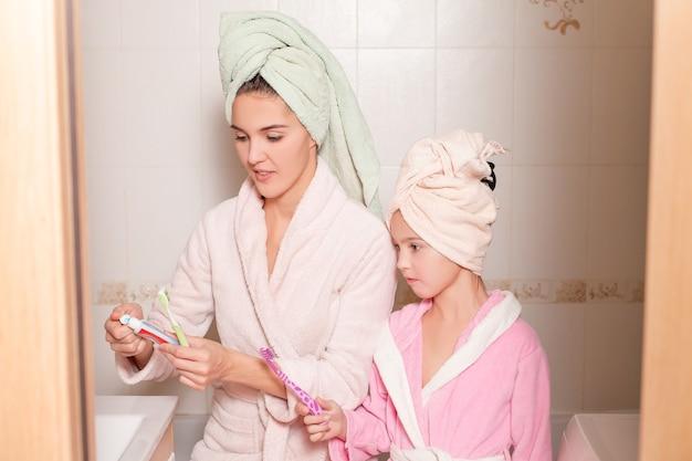 Sourire mère et fille se brosser les dents.