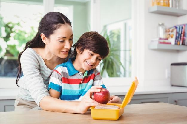 Sourire mère et fils avec boîte à lunch