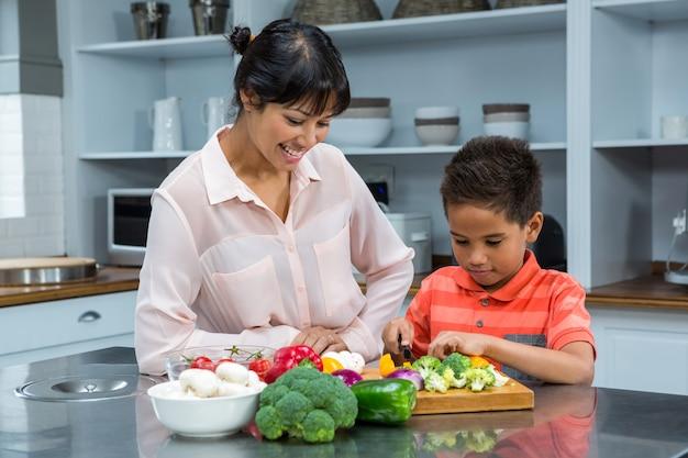 Sourire mère en regardant son fils couper des légumes
