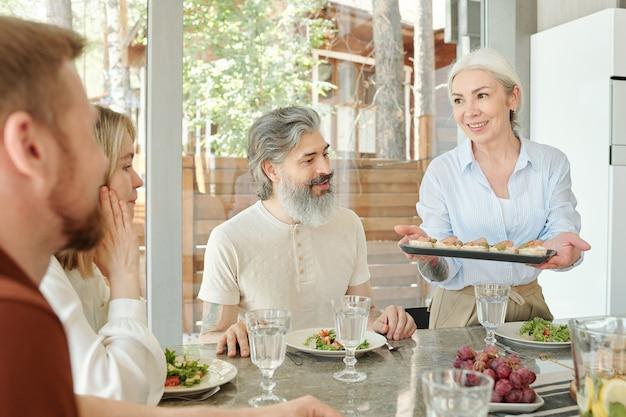Sourire mère senior prudente donnant des apéritifs à la famille pendant qu'ils dînent ensemble dans la salle à manger