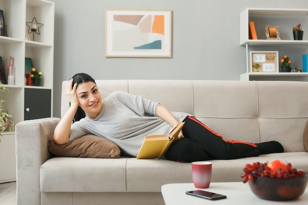 Sourire mettant la main sur la joue jeune fille tenant un livre allongé sur un canapé derrière une table basse dans le salon
