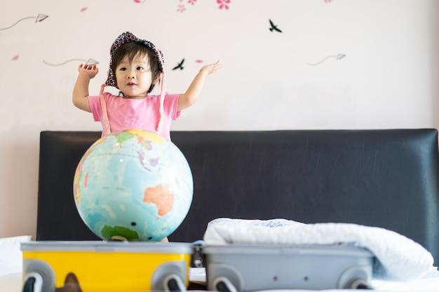 Sourire mignon asiatique petite petite fille portant un chapeau debout sur le lit, se sentir drôle, rire et danser dans la chambre.
