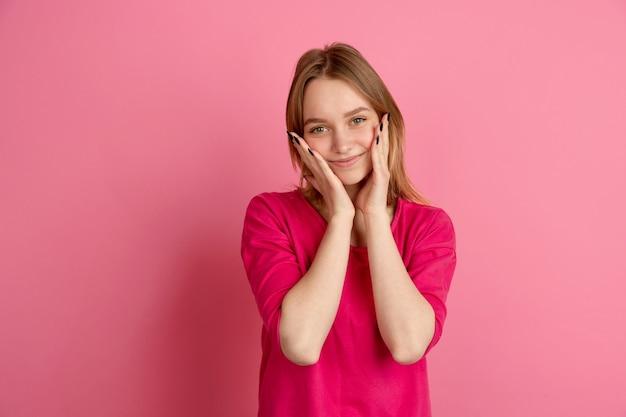 Sourire mignon, heureux. portrait de jeune femme caucasienne sur studio rose