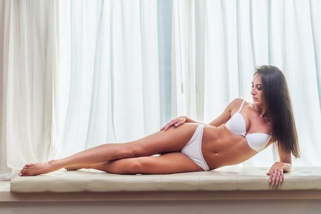 Sourire mince jeune femme brune vêtue de lingerie blanche allongée sur le canapé dans une pièce lumineuse au-dessus de la grande fenêtre.