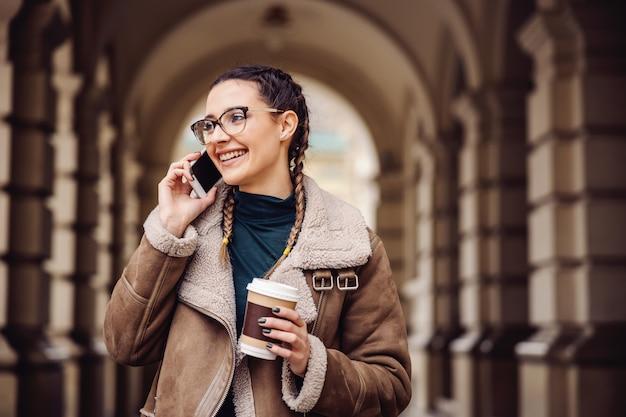 Sourire à la mode étudiante debout sur le campus, tenant une tasse jetable avec du café et ayant une conversation téléphonique.