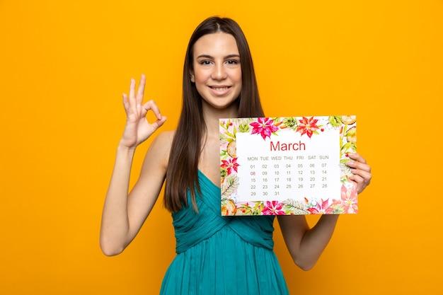 Sourire montrant un geste correct belle jeune fille le jour de la femme heureux tenant le calendrier