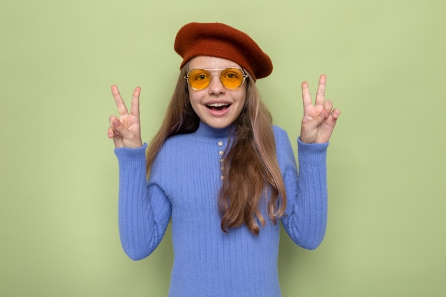 Sourire montrant un geste de paix belle petite fille portant un chapeau avec des lunettes isolées sur un mur vert olive