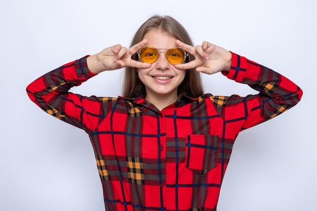Sourire montrant un geste de paix belle petite fille portant une chemise rouge et des lunettes isolées sur un mur blanc
