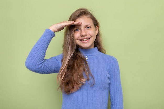 Sourire montrant le geste de salut belle petite fille portant un pull bleu isolé sur un mur vert olive