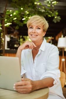 Sourire, mûrir, femme, séance, café, ordinateur portable