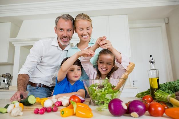 Sourire, parents, enfants, préparer, salade légume, cuisine