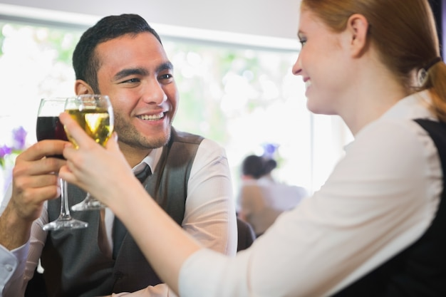 Sourire de partenaires commerciaux tinter les verres de vin