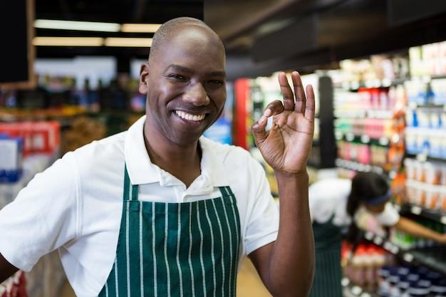 Sourire, personnel masculin, debout, dans, supermarché