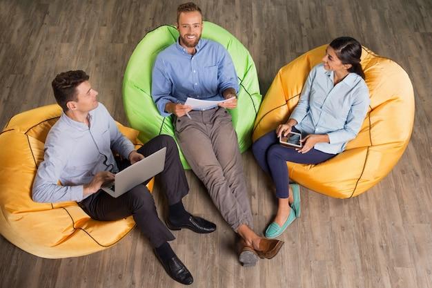 Sourire personnes de travail sur les chaises lumineux beanbag
