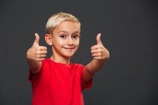 Sourire petit enfant garçon montrant les pouces vers le haut.