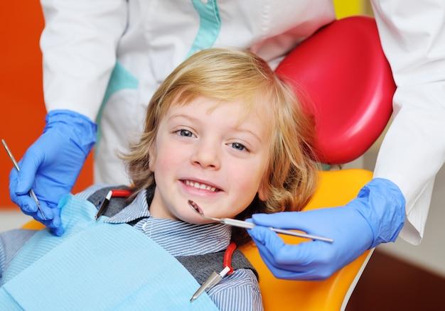 Sourire de petit garçon aux cheveux blonds bouclés en fauteuil dentaire.