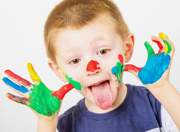 Sourire de petit garçon aux mains peintes dans des peintures colorées