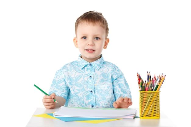 Sourire petit garçon dessine avec des crayons isolés sur blanc