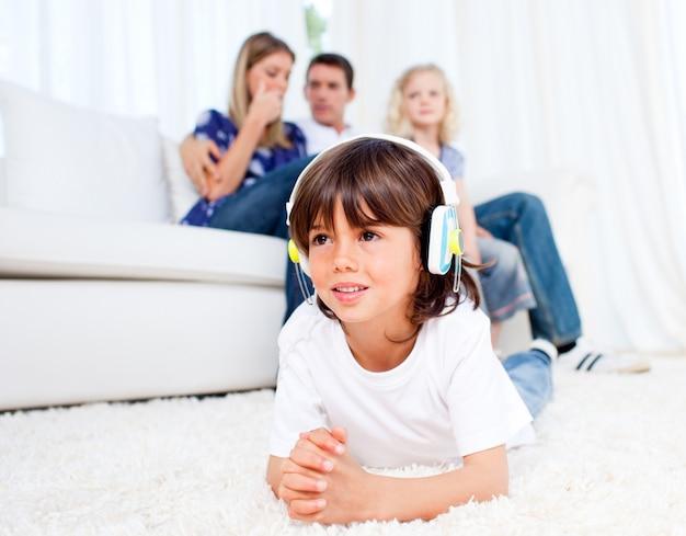 Sourire petit garçon écoute la musique gisant sur le sol
