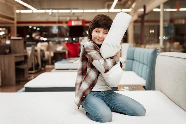 Sourire petit garçon étreignant oreiller sur le lit en magasin