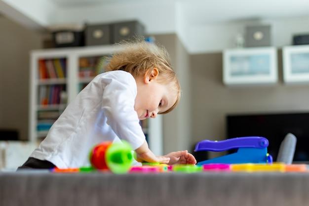Sourire petit garçon moules de pâte à modeler colorée sur table