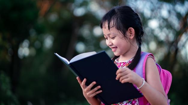 Sourire, petite école, lecture, livre, à, backpack., retour, à, école, concept
