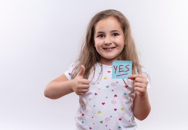 Sourire petite écolière portant un t-shirt blanc tenant du papier marque son pouce vers le haut sur fond blanc isolé