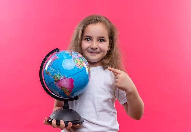 Sourire petite écolière portant un t-shirt blanc tenant un globe sur fond rose isolé