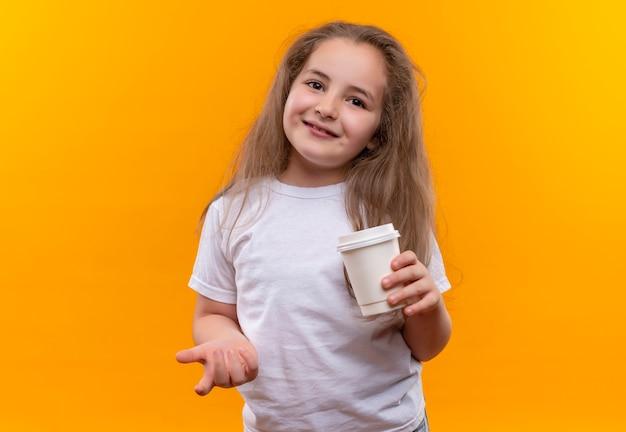 Sourire petite écolière portant un t-shirt blanc tenant une tasse de café sur fond orange isolé