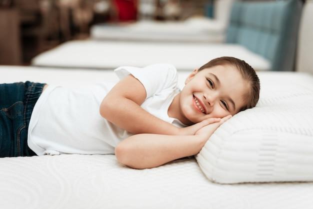 Sourire de petite fille allongée sur le lit dans un magasin de matelas