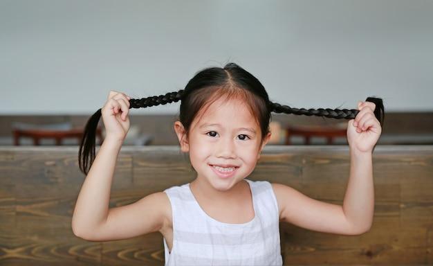 Sourire petite fille asiatique tenant ses cheveux couettes sur la table en bois avec regarder la caméra.