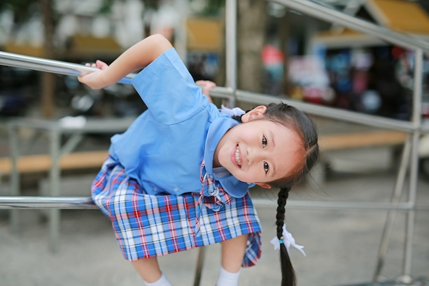 Sourire de petite fille asiatique en uniforme scolaire espiègle suspendu à une rambarde en métal.