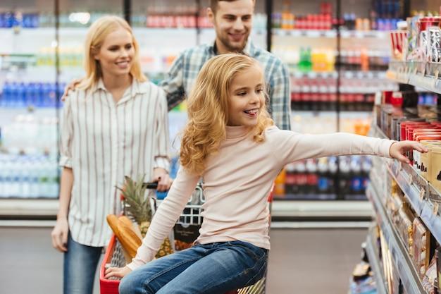 Sourire de petite fille assise sur un panier d'achat