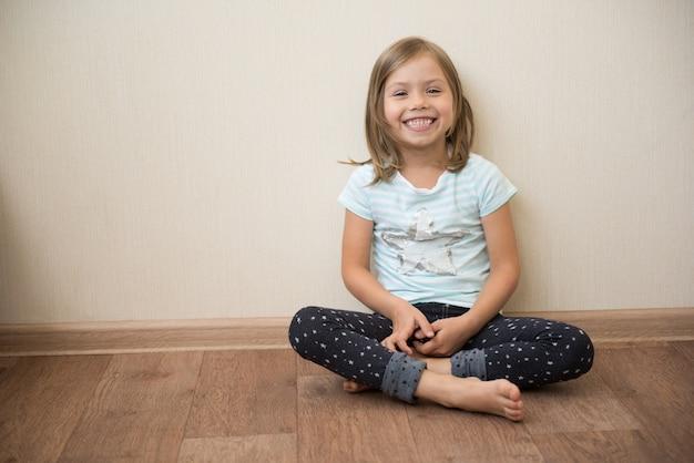 Sourire de petite fille assise pieds nus sur un plancher en bois