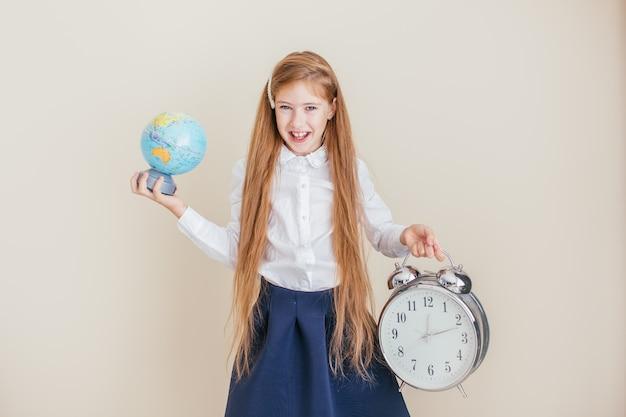 Sourire de petite fille aux cheveux longs tenant une grande horloge et un globe sur fond neutre. gestion du temps, délai, temps pour étudier, école et concept de voyage