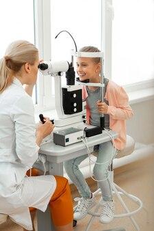 Sourire de petite fille en chemise rose assis devant un médecin attentif