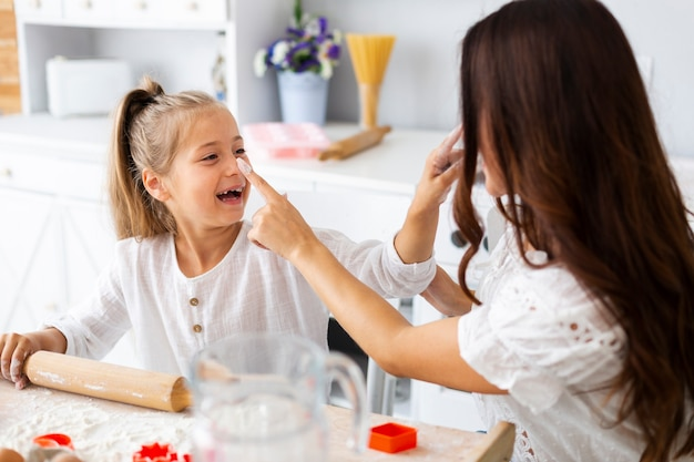 Sourire de petite fille cuisine avec sa mère