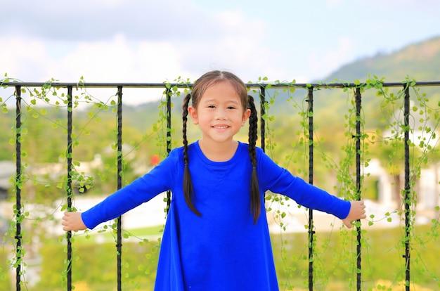 Sourire de petite fille debout aux barres de balcon et regardant la caméra au matin.