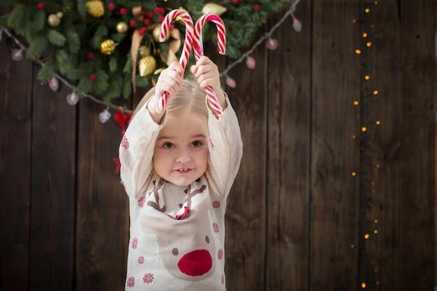 Sourire de petite fille avec des décorations de noël sur bois foncé
