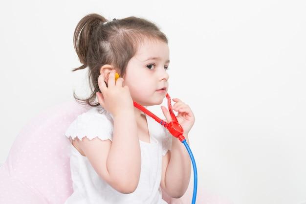Sourire, petite fille, jouer, docteur, et, écoute, à, stéthoscope, isolé, blanc