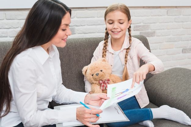 Sourire de petite fille montrant un dessin à la psychologue