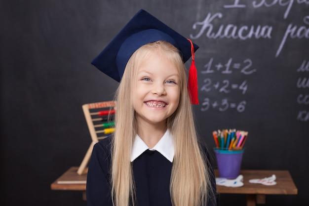 Sourire de petite fille portant un bonnet de graduation à l'école