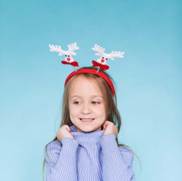 Sourire de petite fille posant sur fond bleu
