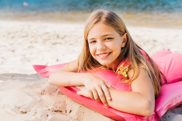 Sourire de petite fille se détendre sur un matelas pneumatique sur la plage en été
