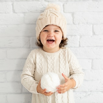 Sourire de petite fille tenant une boule de neige