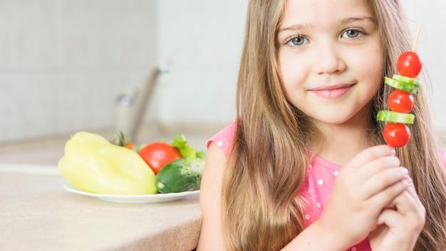 Sourire de petite fille tenant la brochette de salade à la main